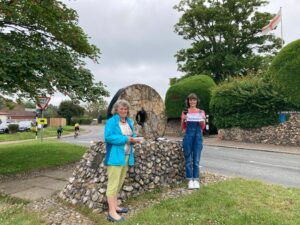 Chair of Parish Council stands by village sign with radio broadcaster